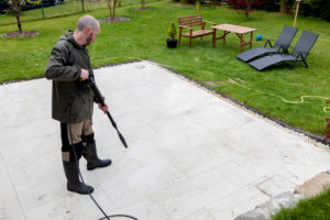 man cleaning patio with pressure washer